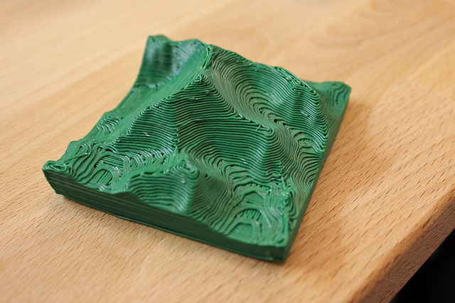 A small green 3D-printed model of Mt. Everest