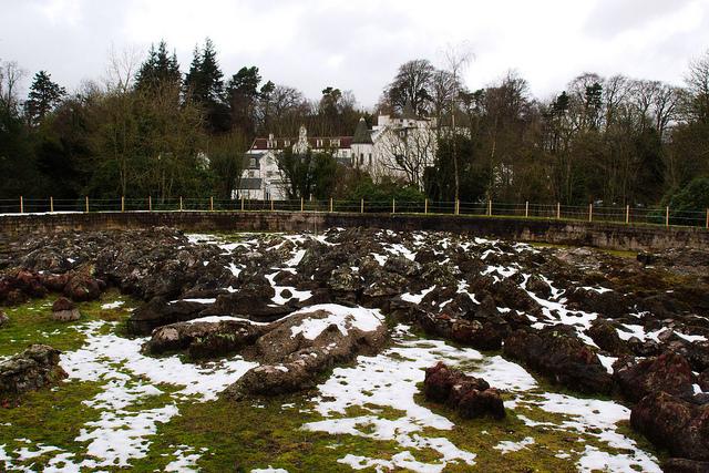 A huge map of Scotland made of snow-covered concrete chunks in a field