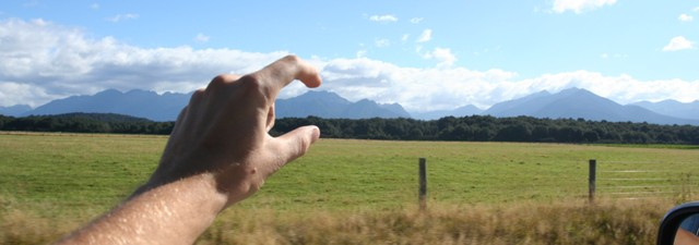 A hand squishing a mountain range's head
